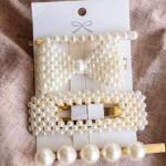Lot quatre pinces à cheveux en métal doré avec des perles d'imitation appliquées.