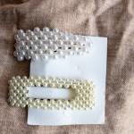 Set de deux barrettes à cheveux en métal doré avec des perles d'imitation appliquées.